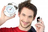 image of tick tock  - Man holding alarm clock and mobile - JPG