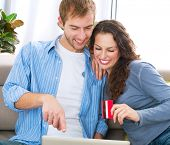 Online Christmas Shopping.Happy Smiling Couple Using Credit Card to Internet Shop on-line. Young cou