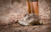 stock photo of wet feet  - Closeup of mud race runner - JPG