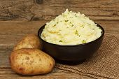 stock photo of whipping  - serving of creamy mashed potato made from boiled potatoes mixed with butter and served in a black bowl on a traditional rustic background - JPG