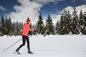 stock photo of nordic skiing  - A woman cross-country skiing in the Alps