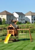 stock photo of swingset  - Back Yard Wooden Swing Set on Green Lawnvertical - JPG