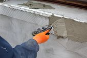 image of trowel  - Worker spreading mortar over styrofoam insulation with trowel - JPG