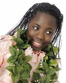 Close-up of a beautiful black tween girl with a lei of leaves around her neck.  On a white backgroun