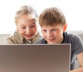 foto of young boy  - Little boy and girl portrait sitting at notebook - JPG