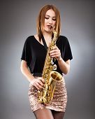 pic of saxophone player  - Beautiful blond woman saxophone player studio closeup shot - JPG