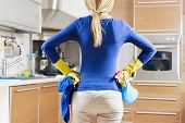 foto of disinfection  - rear view of woman with yellow gloves in kitchen doing housework - JPG
