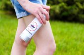 picture of mosquito repellent  - Woman spraying insect repellent on skin - JPG