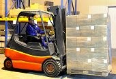 pic of forklift driver  - Worker driver of a forklift loader in blue work wear at warehouse with cardboard boxes on pallet - JPG