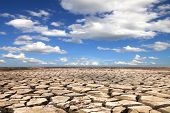 stock photo of drought  - Drought land against a blue sky with clouds - JPG