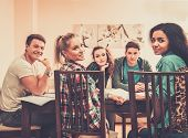 picture of exams  - Multi ethnic group of students preparing for exams in home interior behind table  - JPG