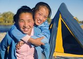 picture of mongolian  - Happy Mongolian girls playing piggyback at campsite - JPG