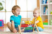 image of pretty-boy  - happy kids boys playing with abacus toy indoors - JPG