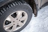 picture of stud  - Modern automotive wheel with studded tires and winter snowy road - JPG