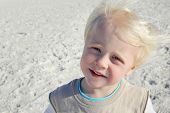 picture of windy  - A portrait of a happy little two year old boy child smiling at the camera while at the beach on a windy summer day - JPG