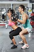 stock photo of squatting  - Personal trainer helping a young woman doing squat exercises with barbell in a gym - JPG