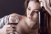 stock photo of forlorn  - Young beautiful woman in depression drinking alcohol