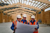 stock photo of purlin  - A team of builders discuss the plans for a major construction job - JPG