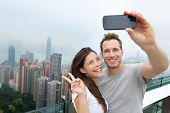 pic of selfie  - Hong Kong Victoria Peak tourists couple taking selfie photo picture with smartphone enjoying view over Hong Kong and Victoria Harbour - JPG