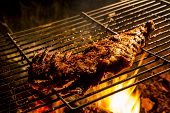 stock photo of ribs  - delicious Ribs in BBQ Grill with flames in background - JPG