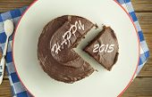 foto of chocolate fudge  - Chocolate covered fudge cake with 2015 new year slice - JPG