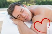 picture of peaceful  - Peaceful man lying on massage table poolside against heart - JPG
