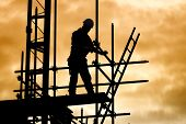 image of structural engineering  - silhouette of construction worker against sky on scaffolding with ladder on building site at sunset - JPG