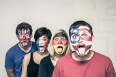 stock photo of sticking out tongue  - Group of funny people with painted flags on their faces and sticking out tongue - JPG