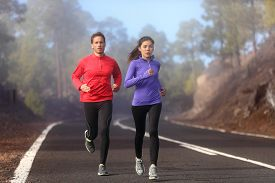 stock photo of male female  - Healthy running runner man and woman workout on mountain road - JPG