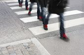 pic of zebra crossing  - Young man in sneakers with red shoe laces in blurred motion crossing street - JPG