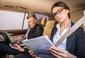 foto of personal assistant  - Mature businessman in suit sitting in the car with his beautiful personal assistant and using laptop - JPG