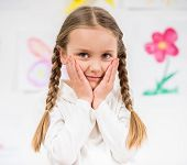 stock photo of pullovers  - Little pretty smiling girl in white pullover at home on colorful background - JPG