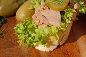 picture of baguette  - Slice of baguette with tuna fillet garnished with lettuce onion tomato and pickles on a wooden board - JPG