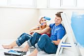 picture of wall painting  - Charming couple relaxing after painting a room in their new house - JPG