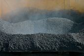 pic of hopper  - steam rises from hot asphalt in the hopper of a paving machine - JPG
