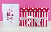 stock photo of special day  - Happy Mothers Day pink and white gift with Best Mom Ever greeting card on white shabby chic distressed wood table - JPG