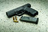 stock photo of ammo  - Gun with magazine and ammo on floor - JPG
