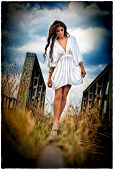 stock photo of cross-dress  - Sensual girl with white dress walking on the railway under the blue sky - JPG
