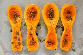 stock photo of butternut  - Four butternut squash pieces with pumpkin seeds on white paper horizontal topview - JPG