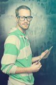 stock photo of nerd  - Good Looking Young Nerd Smart Guy Man Using Tablet Computer - JPG