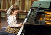 image of grand piano  - Cute little girl playing grand piano in music school childhood concept - JPG