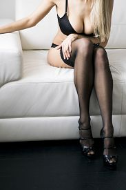 image of stocking-foot  - Sexy Woman in black stockings on sofa with high heels resting on sofa  - JPG