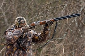 stock photo of hunter  - hunter in camouflage takes aim from a gun - JPG