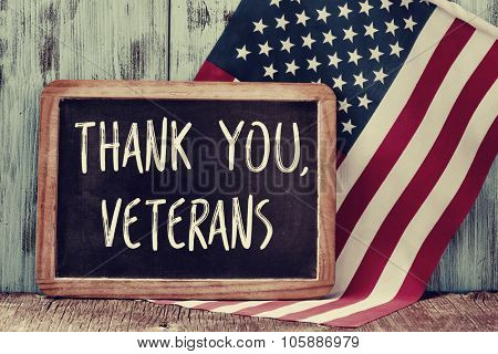 the text thank you veterans written in a chalkboard and a flag of the United States, on a rustic woo