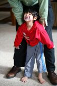 stock photo of physically handicapped  - Father helping his disabled son to walk