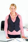 Friendly modern business woman standing near office desk