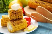 Tasty Grilled Corns With Butter And Tomatoes On Blue Wooden Table poster