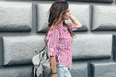 Fashion model wearing red striped shirt and backpack posing in the city street. Fashion urban outfit poster