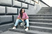 Fashion model wearing ripped boyfriend jeans, red striped shirt, sneakers and backpack posing in the poster