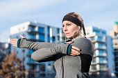 Portrait of a determined young woman stretching her left arm during warm-up routine before outdoor w poster